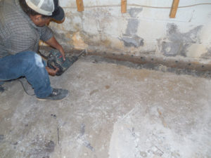 drilling holes in cinder block to release water pressure